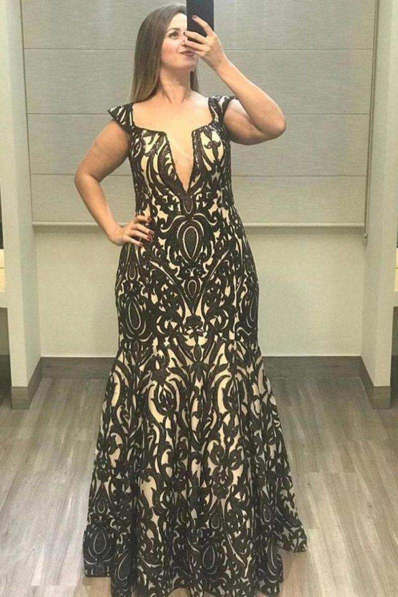 modelo plus size vestindo vestido de festa preto e nude.